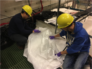 Jingbo and Marcus are cleaning a Hefty bag to use in the tank.